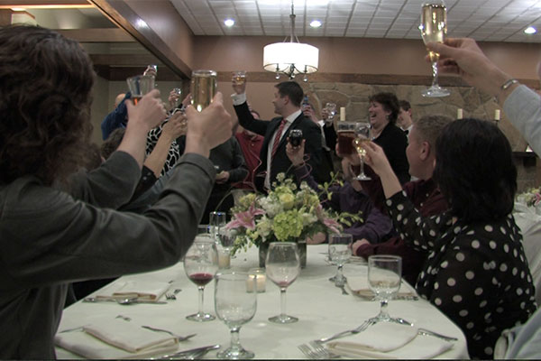 many people raising glasses as a toast
