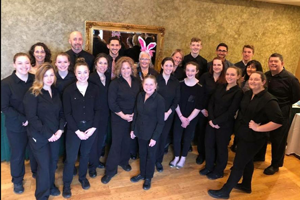 large staff dressed in black with one woman wearing bunny ears