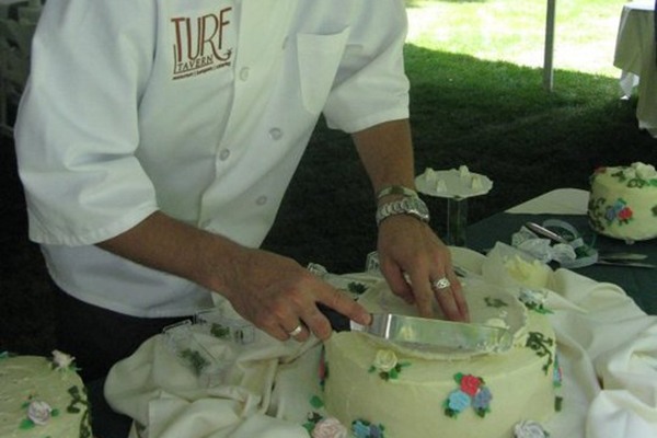man icing cake outside under a tent
