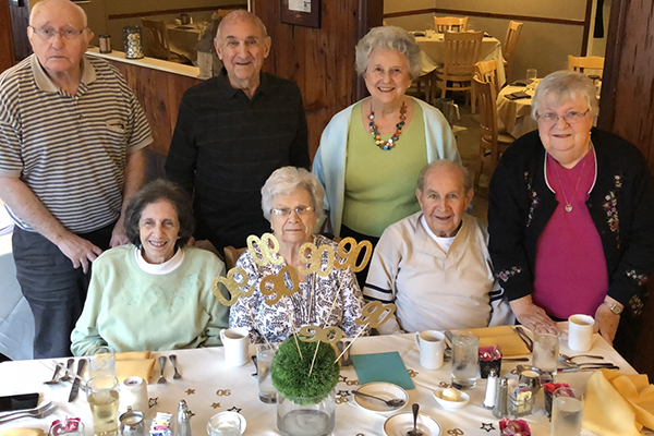 seven individuals around a birthday cake to celebrate a 90th birthday