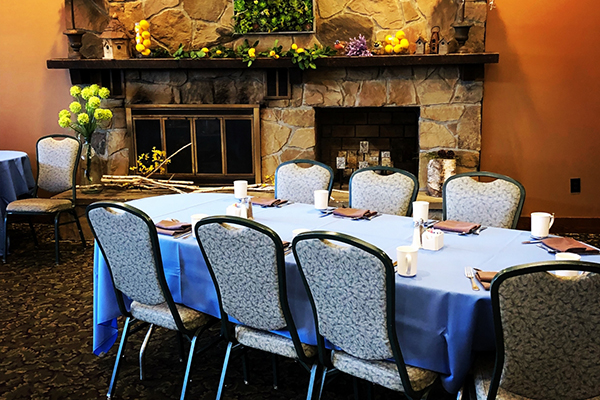 event space with blue tablecloths and fireplace in the background
